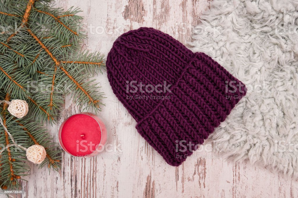 Purple hat. Spruce branch, garland and candle. Wooden background. New Year's concept. stock photo