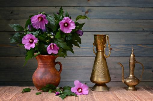 Purple hibiscus in a ceramic vase
