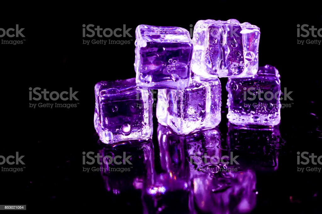 Purple ice cubes on a black table. stock photo