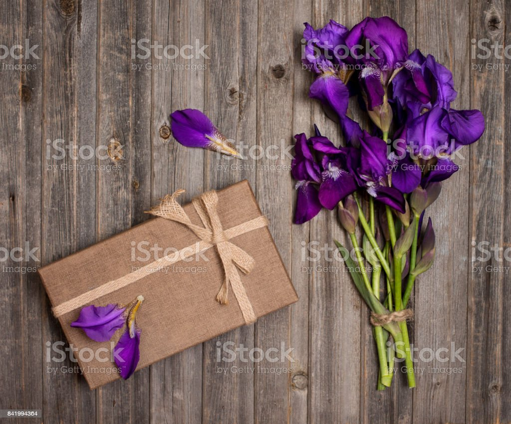 Purple Iris Flowers Bouquet And Gift Box On Weathered Wooden