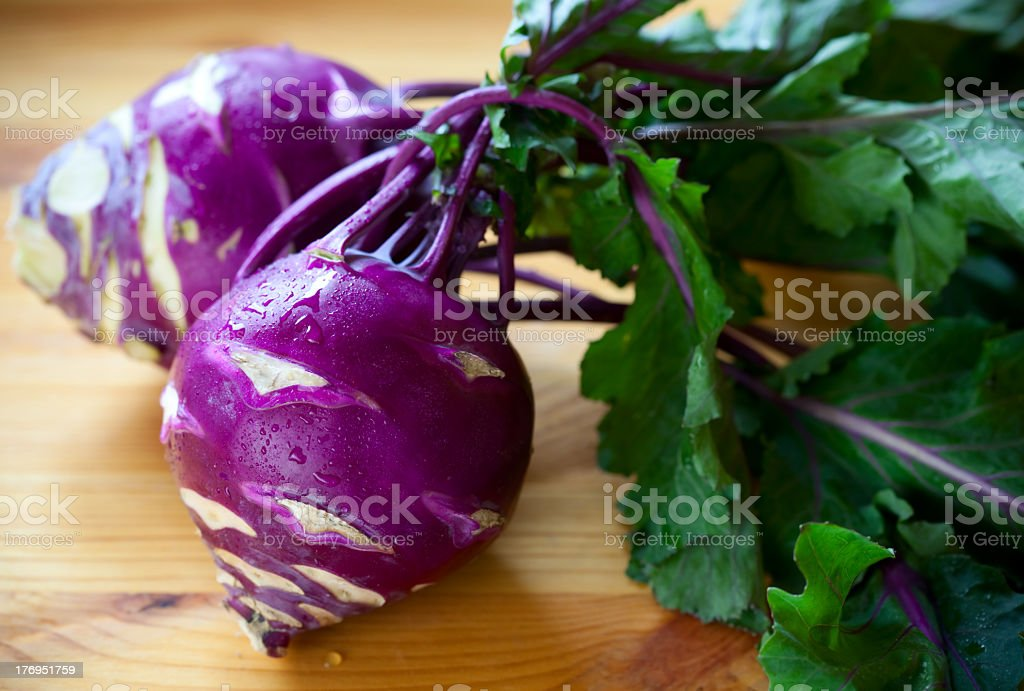 Purple kohlrabi with foliage on a wooden board stock photo