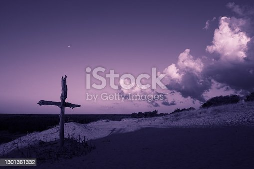 istock Purple landscape with wooden Cross or crucifix.  Concept for Lent Season, Holy Week, Palm Sunday and Good Friday. 1301361332
