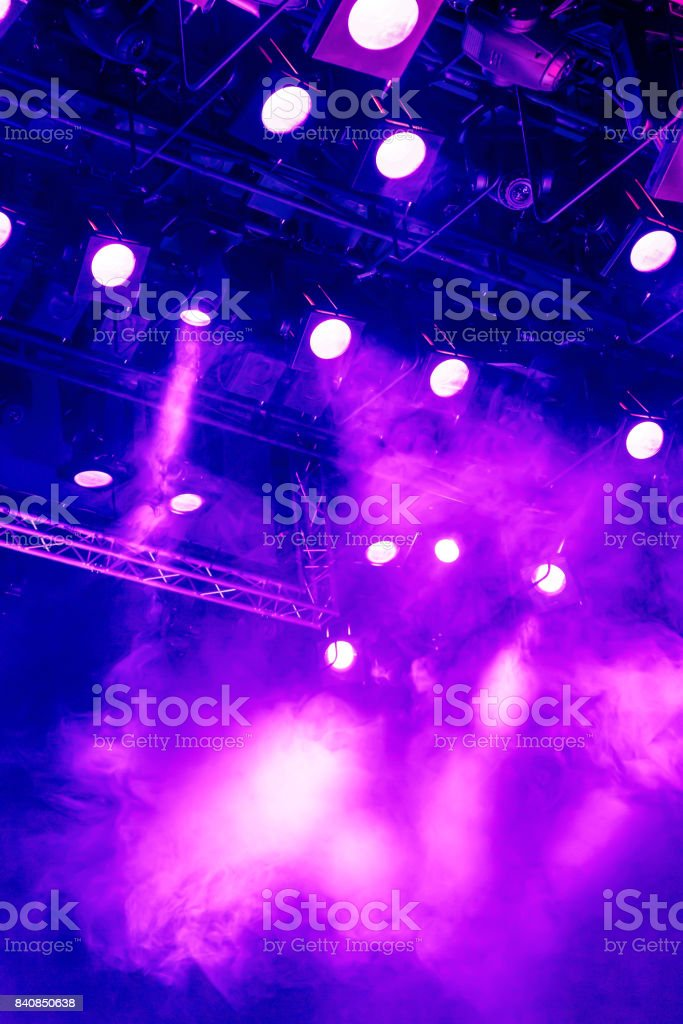 Purple light rays from the spotlight through the smoke at the theater...