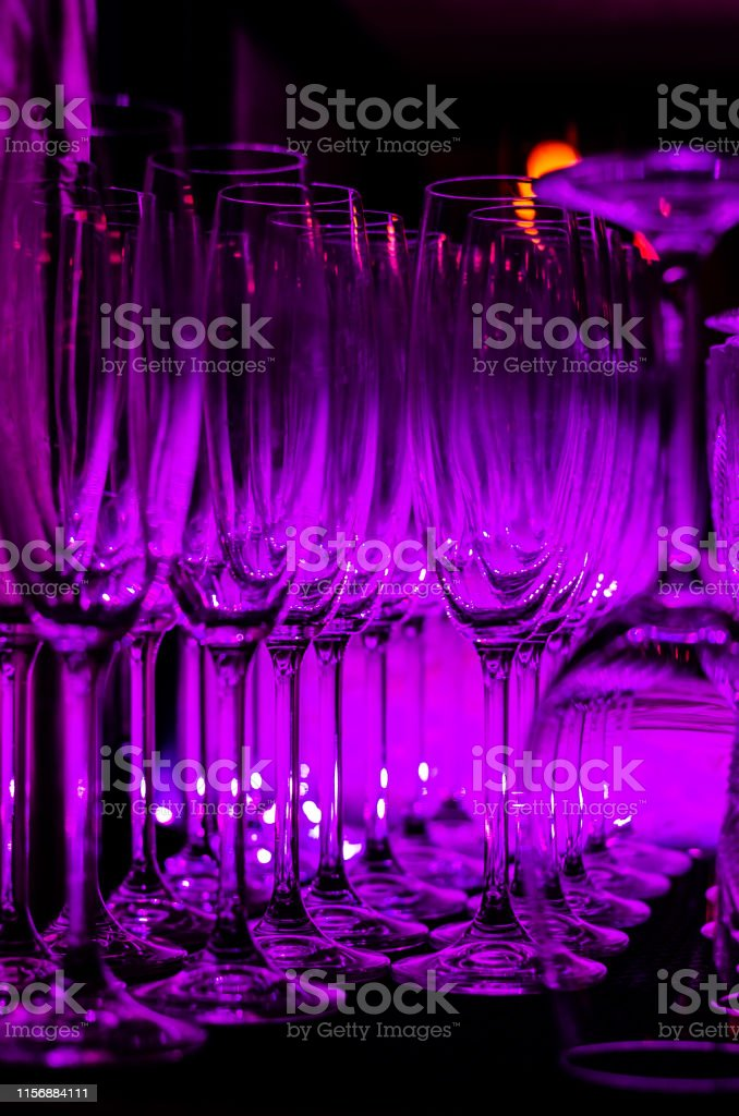 Purple light reflected in the rows of empty clean glasses on the bar...