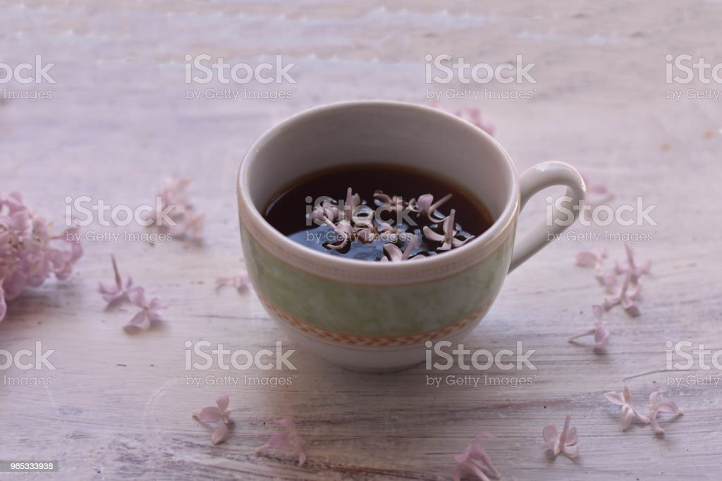 Purple lilac flowers and cup of tea on light wooden background/ teatime/ spring background/ cozy at home/ home spring decoration royalty-free stock photo