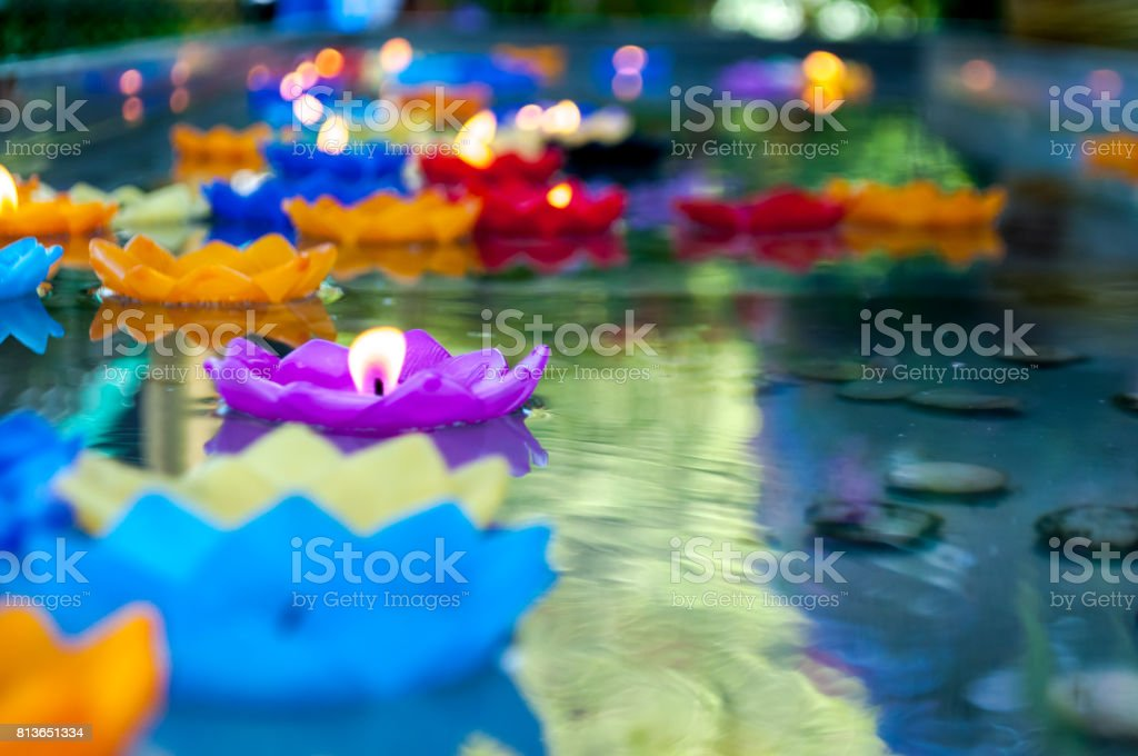 Purple lotus shape candle lit and float on water stock photo