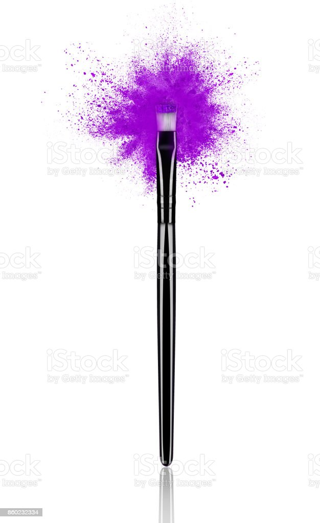 Purple make up brush with powder splash close-up, isolated on white background stock photo