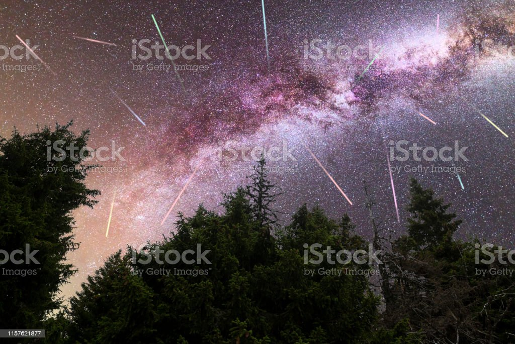 A view of a Meteor Shower and the purple Milky Way with pine trees...