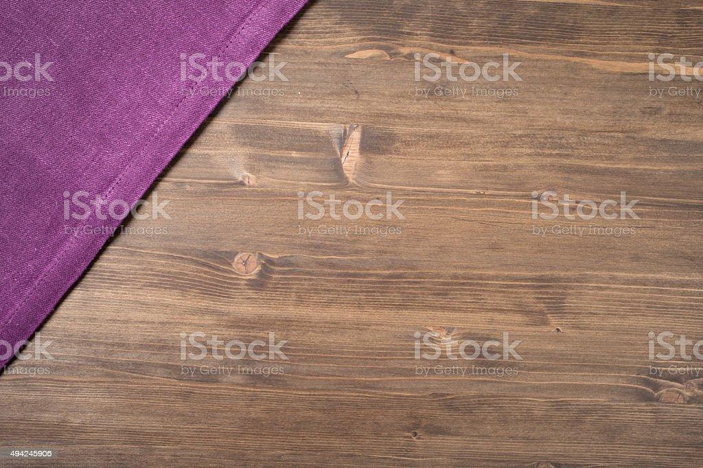Фиолетовый napkin в левом верхнем углу деревянном столе стоковое фото
