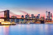 Brooklyn Bridge and the Lower Manhattan skyline under a purple sunset