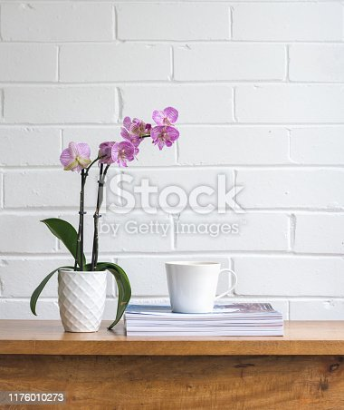 Closeup of purple moth orchid, white cup and magazines on oak table against painted brick wall (selective focus)