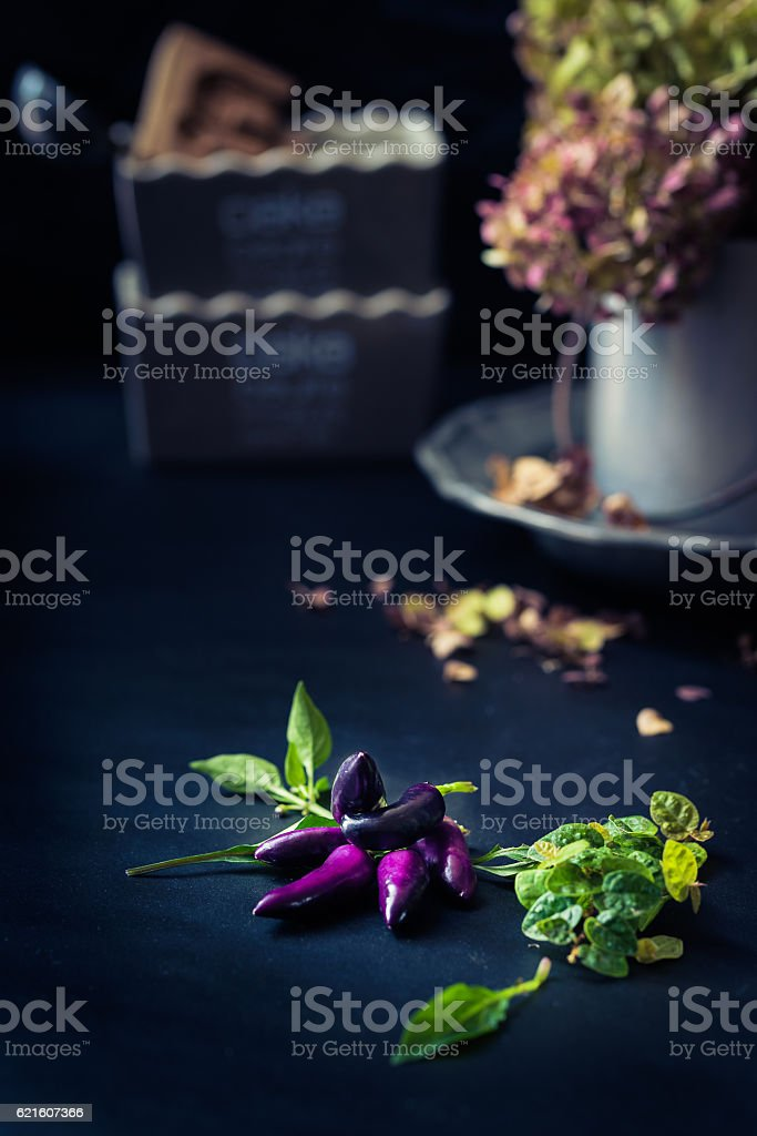 purple peppers with leaves, withered flowers and cake pans blurred stock photo