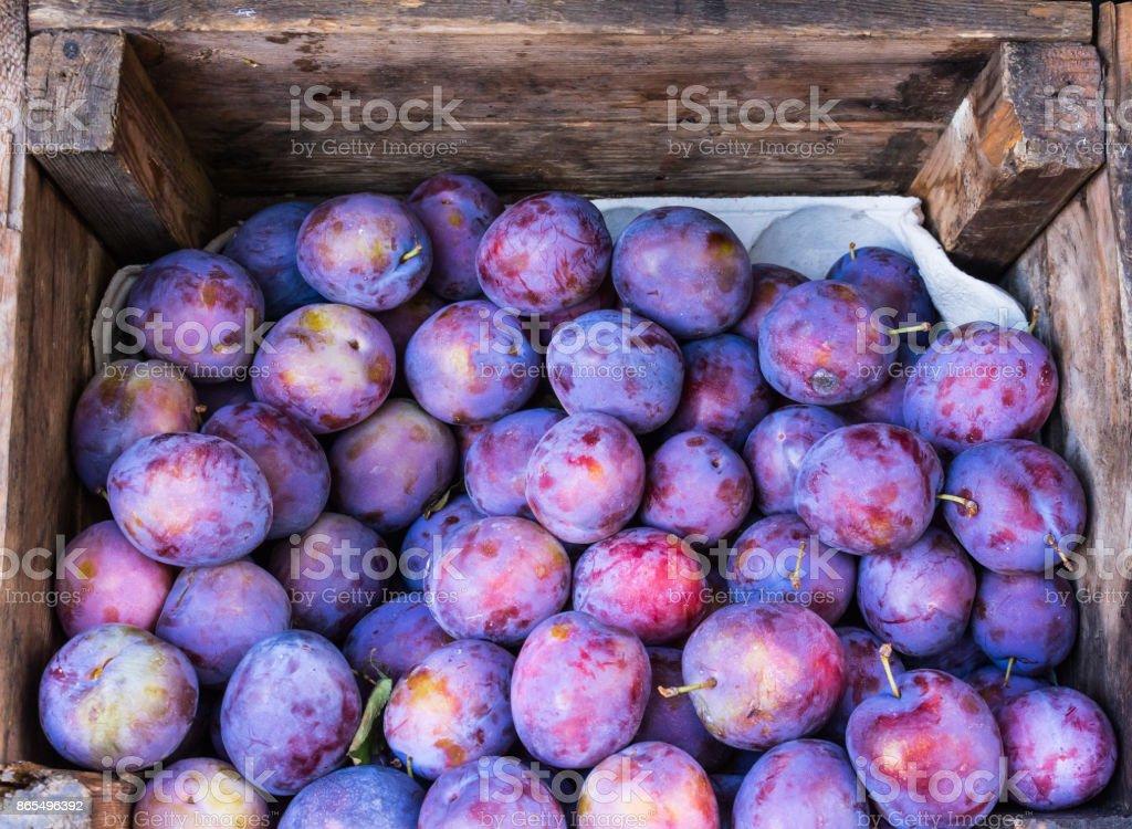 ameixas roxas em caixa de madeira - foto de acervo