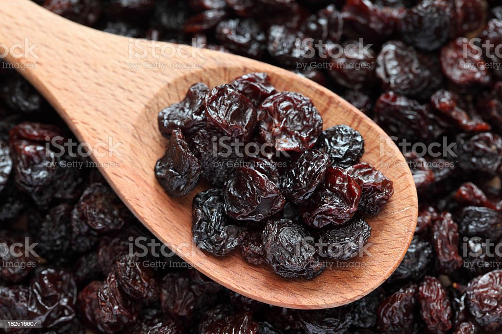 Purple raisins on a wooden spoon stock photo