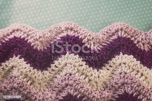 Stripes of pink, purple, and white in a crocheted afghan, laying against a light blue polka dot background.