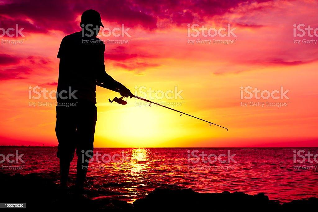 Purple sea sunset and fisherman royalty-free stock photo
