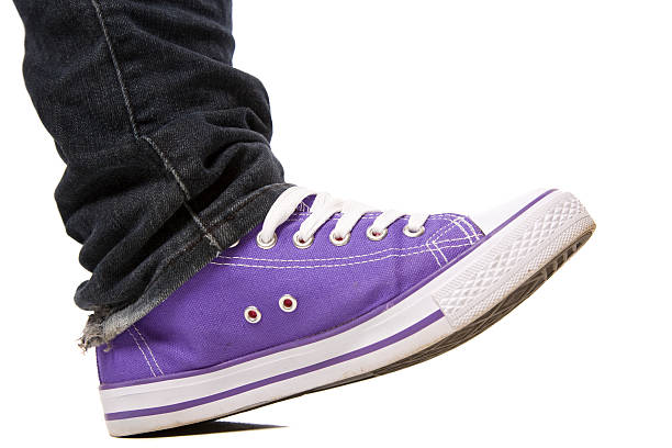 Purple Shoe Stepping A purple canvas sport shoe stepping forward isolated on white with shadow. stepping stock pictures, royalty-free photos & images