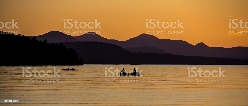 Purple sky at sunset with kayakers and water. stock photo