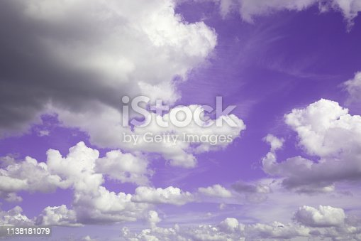 Surrealistic purple sky with fluffy white clouds.