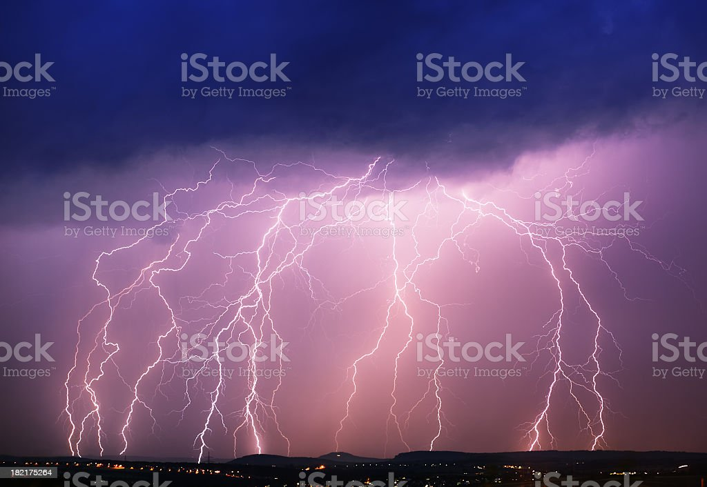 A purple sky with dark clouds and lightning hitting a town royalty-free stock photo