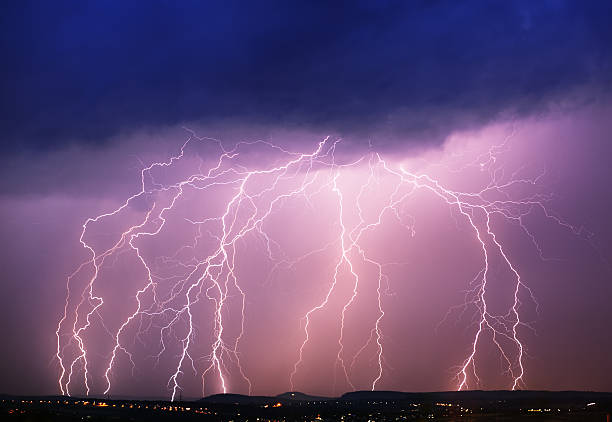 A purple sky with dark clouds and lightning hitting a town stock photo
