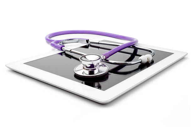 Purple stethoscope on top of white digital tablet stock photo