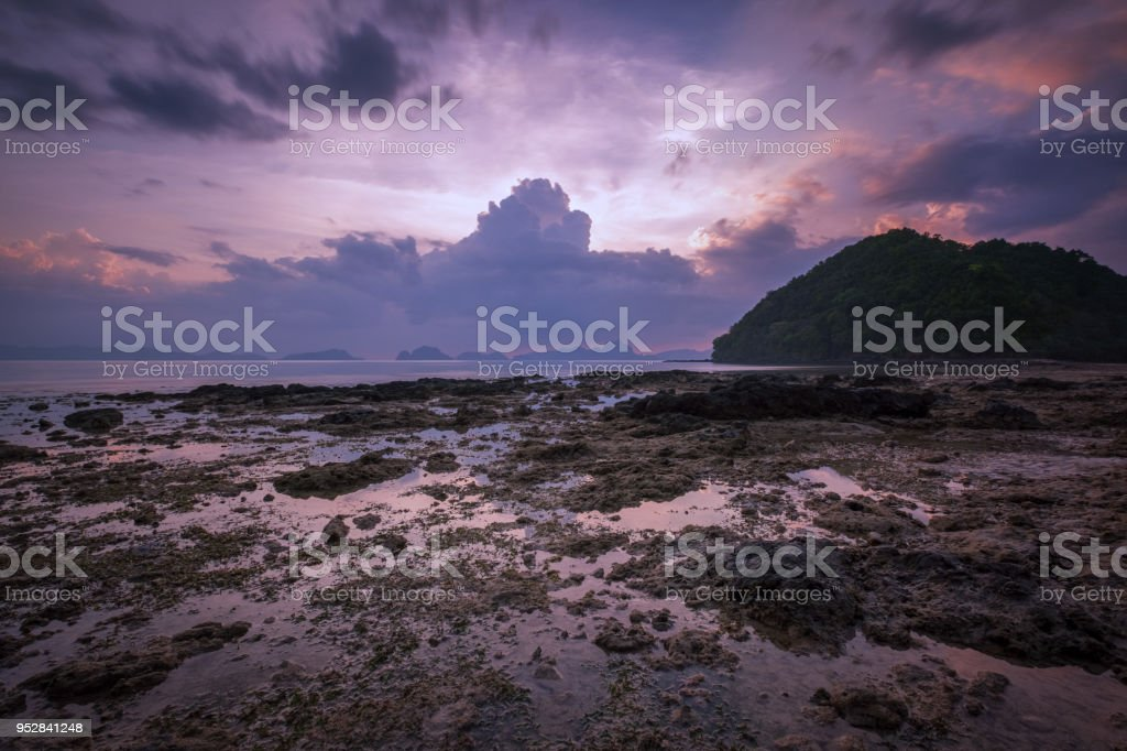 Purple sunset behind clouds over ocean stock photo