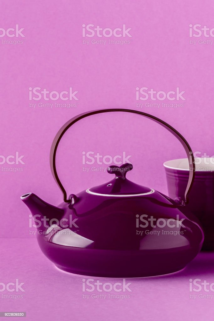 Purple teapot and cups on a lilac background with copy space.