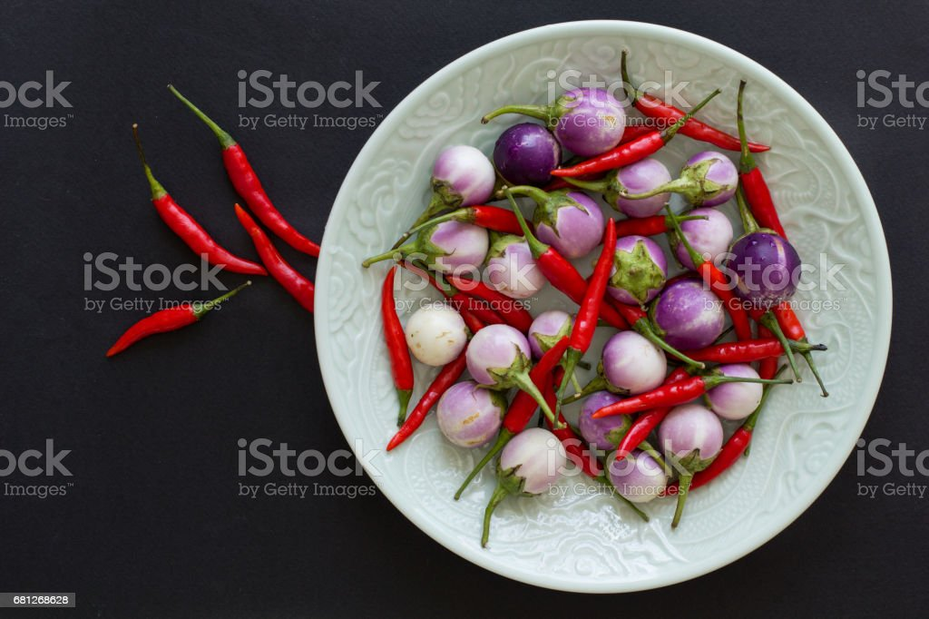 Purple Thai eggplants and hot chili peppers on a green plate and nearby on a black background. Asian food. royalty-free stock photo