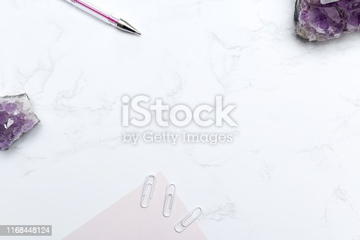 Purple themed stationary set with notebook and pen on a modern marble desk