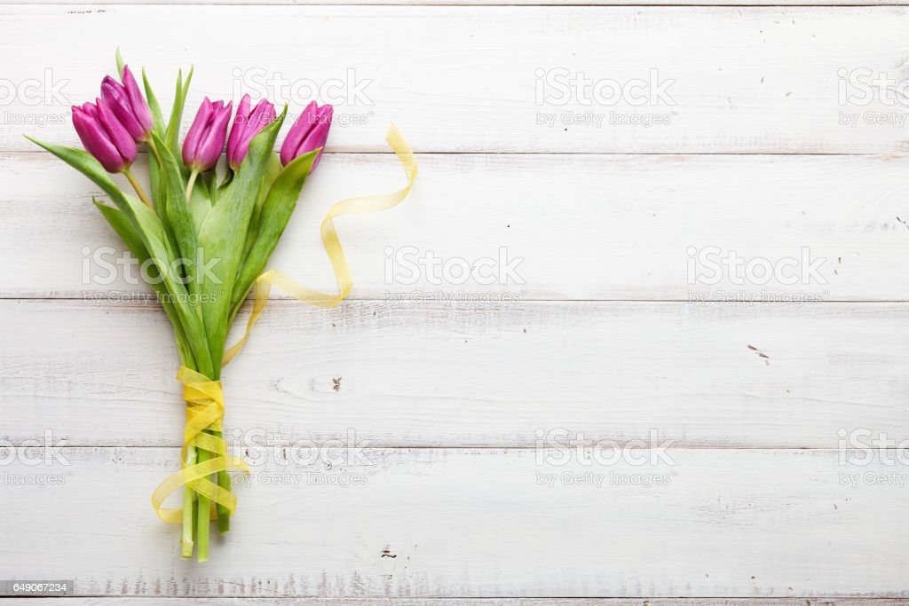 Purple tulips on white wooden boards stock photo