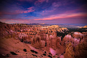 Sunlight disappears from the steep canyons and rock hoodoos of Bryce Canyon National Park on a colorful evening.