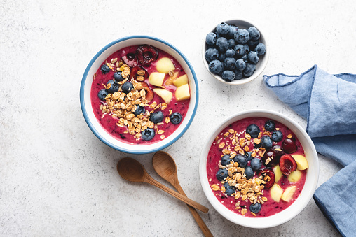 Purple vegan smoothie bowl with blueberries, cherries, peach and granola on grey cement background, top view, copy space. Clean eating concept