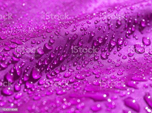 Photo of Purple waterproof fabric with waterdrops close up