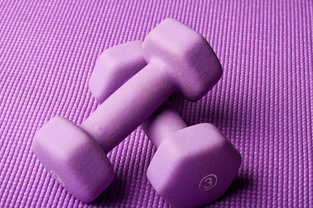 Purple weights on yoga mat stock photo