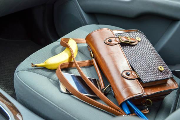 geldbeutle und zubehör, die auf dem pkw-sitze mit einer banana abgelegt werden - handytasche stock-fotos und bilder