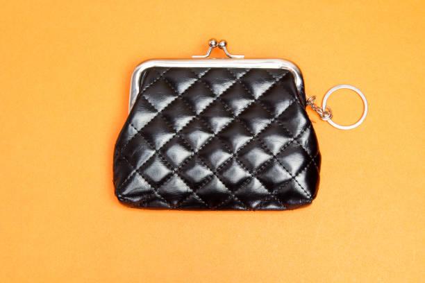 geldbeutel-püree. schwarzer ledertasche auf orangefarbenem hintergrund - rentenpunkte stock-fotos und bilder