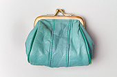 Purse for coins. Wallet for change. Leather purse. Turquoise purse on a grey background. Color of the trend. The concept of poverty