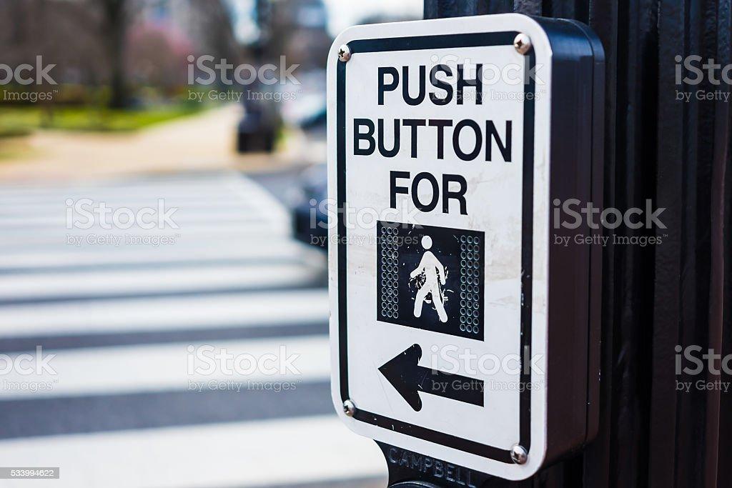 Push button to cross road crosswalk sign stock photo