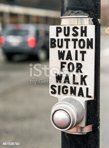 A sign above a crosswalk button in Boston, Massachusetts reading 'Push Button Wait For Walk Signal'
