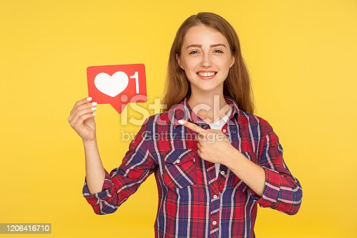 640248524 istock photo Push heart button to enjoy content. Portrait of happy ginger girl in checkered shirt pointing at social media like icon 1206416710