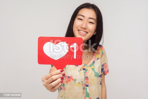 640248524 istock photo Push Like button! Glad cheerful asian girl with charming smile showing social network heart icon, recommending to subscribe 1208160309
