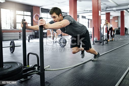 Shot of a young man pushing a weight sled in the gym