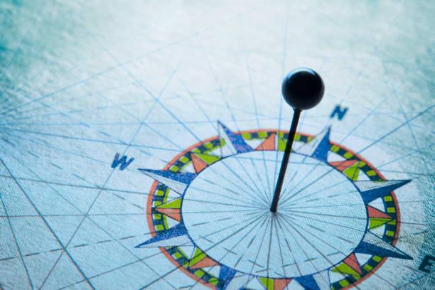 push-pin in der mitte des kompass-rose - kompass wanderkarte stock-fotos und bilder