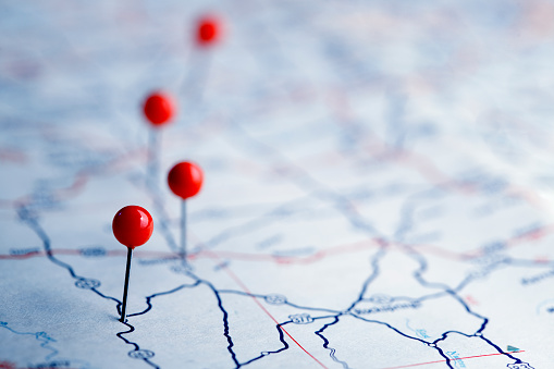 A row of four push pins on a road map.  The road map is very generic with no town names or landmarks legible.  The image is photographed using a very shallow depth of field.