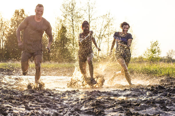 Push the Limits Three young adult athletes are about to cross the finish line after an extreme challenge of running through mud outdoors. Here, the sunset is behind them as they race through muddy water. mud run stock pictures, royalty-free photos & images