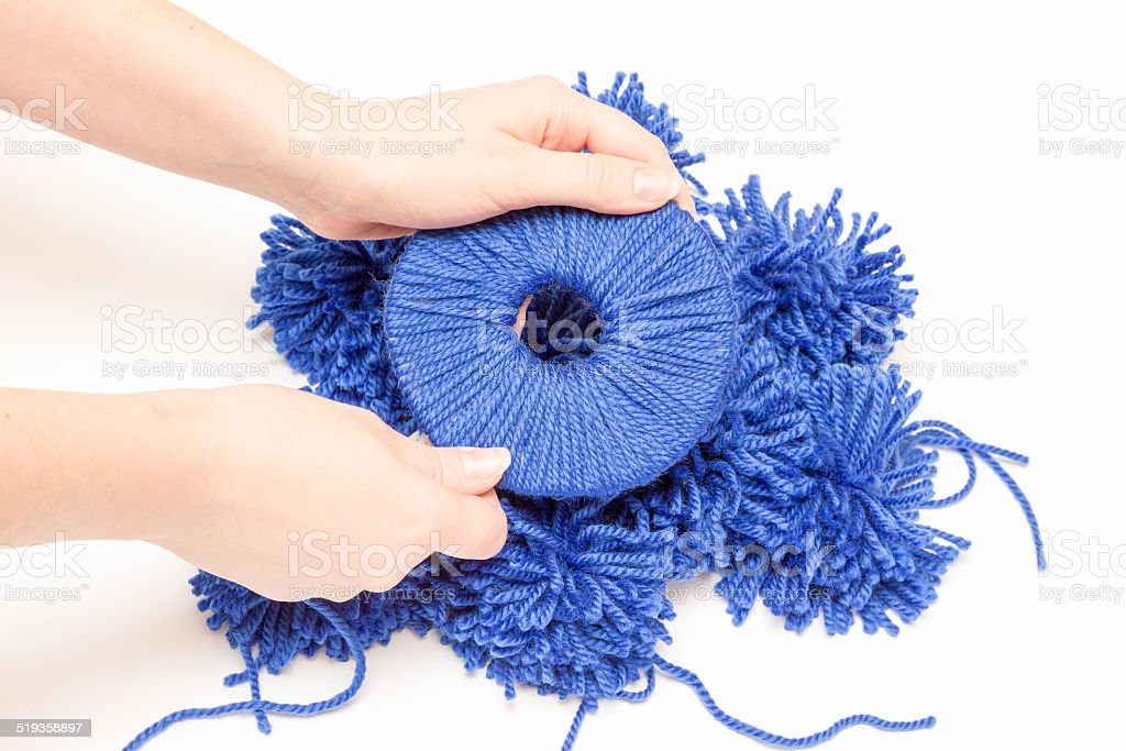 push  thread through  hole in  disc for blue pompon stock photo