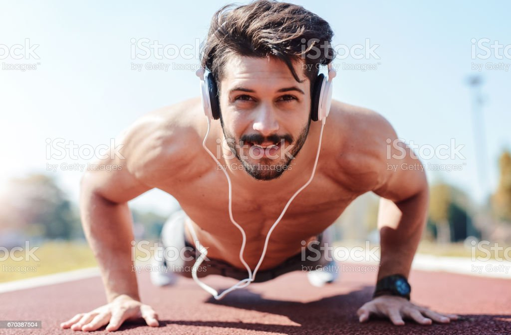 Push ups. Young muscular sportsman doing fitness exercise outdoors. Sport, fitness, street workout concept stock photo