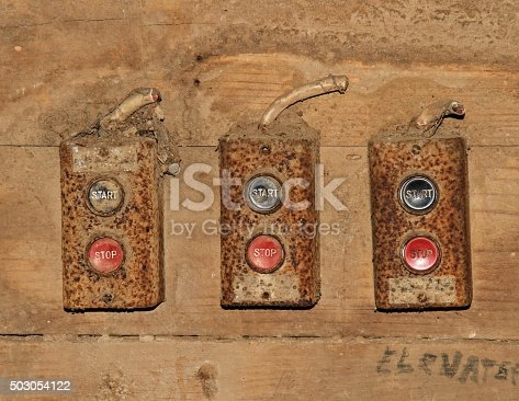 Row of three old pushbotton switches in an old wood mill.