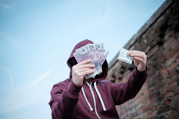 Pusher selling and trafficking drug dose for money cash - foto stock